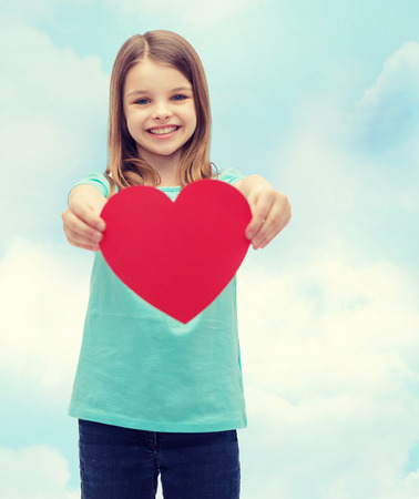 pre teen girls: love, happiness and people concept - smiling little girl giving red heart Stock Photo
