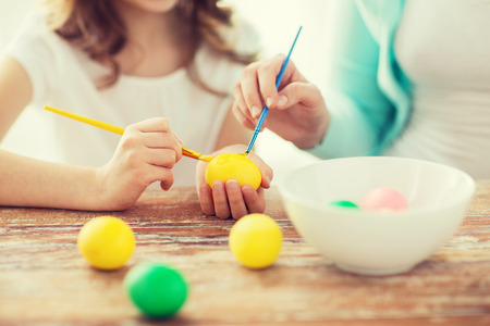 kids painting: easter, family, holiday and child concept - close up of little girl and mother coloring eggs for easter
