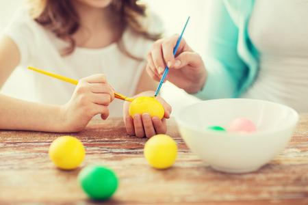 Pascua, la familia, las vacaciones y los niños concepto - cerca de la niña y la madre huevos para la Pascua para colorear