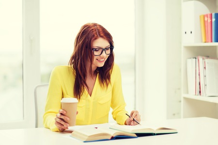 persona escribiendo: concepto de educaci�n - sonriente chica estudiante en gafas de leer libros ana tomando notas en la biblioteca Foto de archivo