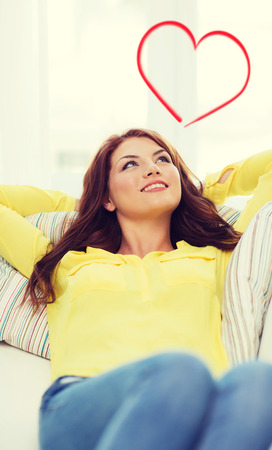 home and happiness concept - smiling young woman lying on sofa at home photo