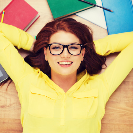 eyeglasses: education and home concept - smiling redhead female student in eyeglasses lying on floor