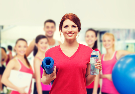 aqua: fitness, home and diet concept - smiling teenage girl with bottle of water and yoga mat after exercising at home