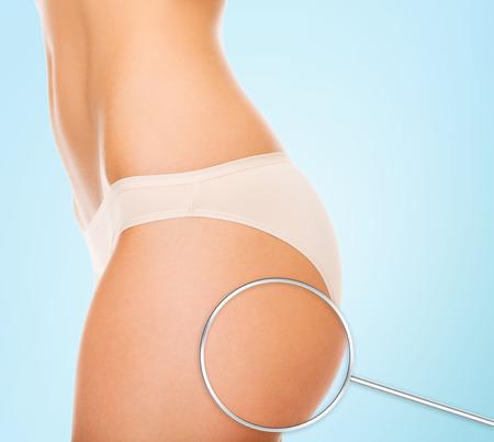 muslos: la salud, las personas, el cuidado corporal y concepto de belleza - cerca de las nalgas de la mujer y de la lupa sobre fondo azul Foto de archivo