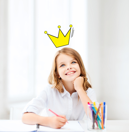 education, creativity, childhood, people and school concept - smiling little school girl drawing and daydreaming at school with crown doodle photo