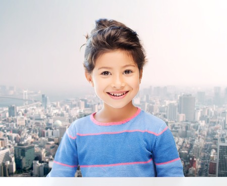 asian preteen: childhood, people and happiness concept - little student girl over city background