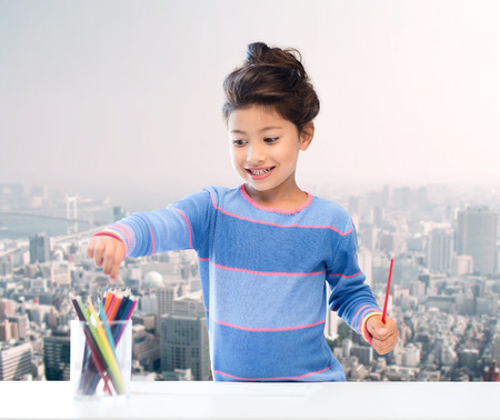 asian art: children, creativity and happy people concept - happy little girl drawing with coloring pencils over city background Stock Photo