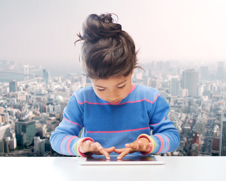 asian preteen: education, technology and children concept - little student girl with tablet pc over city background Stock Photo