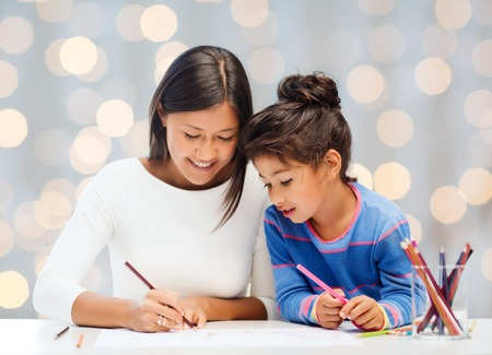 asian preteen: family, children, creativity and happy people concept - happy mother and daughter drawing with pencils over holidays lights background