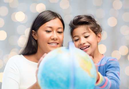 schoolkid search: family, children, education, geography and people concept - happy mother and daughter with globe over holidays lights background