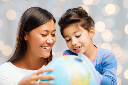family, children, travel, geography and happy people concept - mother and daughter with globe over holidays lights background