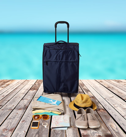 resor: summer vacation, tourism and objects concept - travel bag, map, air ticket and clothes with personal stuff over wooden floor and sea background Stockfoto