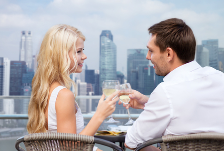 toasting wine: summer holidays, people, honeymoon, vacation and dating concept - couple drinking wine in cafe over city background