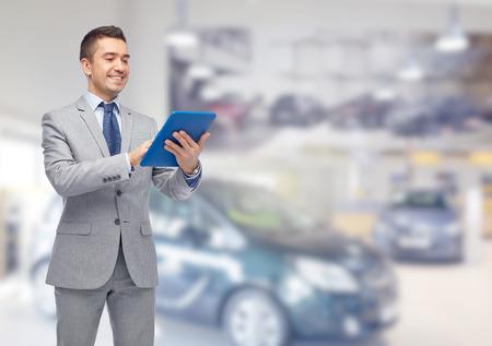 비즈니스, 사람, 자동차 판매 및 기술 개념 - 자동 쇼 또는 살롱 배경 태블릿 pc 컴퓨터를 들고 소송에서 행복 한 미소 사업가