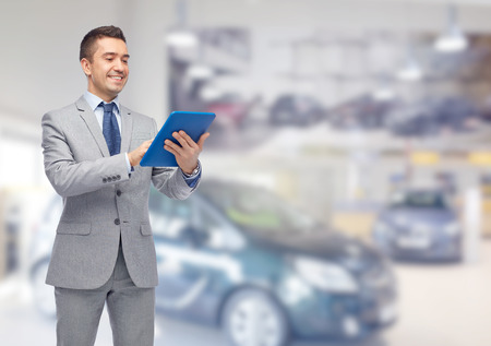 car dealer: business, people, car sale and technology concept - happy smiling businessman in suit holding tablet pc computer over auto show or salon background