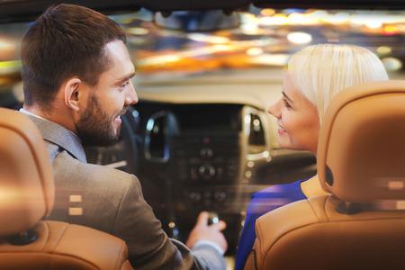 amor, luxo, vida noturna, automóvel e as pessoas conceito - casal feliz dirigindo no carro do cabriolet durante a noite luzes da cidade fundo Imagens