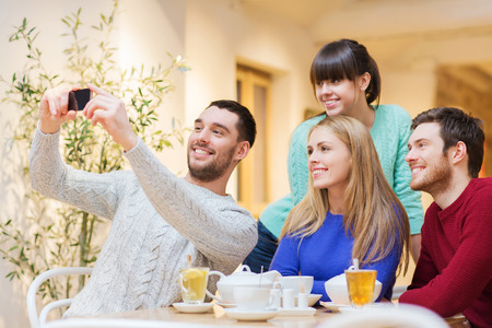 people, leisure, friendship and technology concept - group of happy friends with smartphone taking selfie and drinking tea at cafe photo