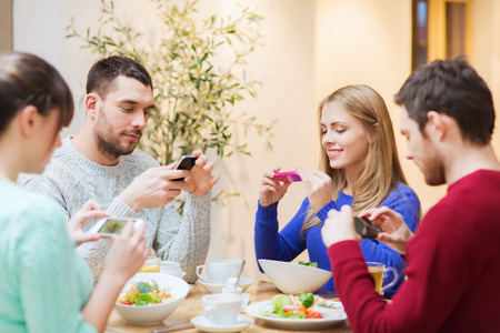 people, leisure, friendship and technology concept - group of happy friends with smartphones taking picture of food at cafe photo