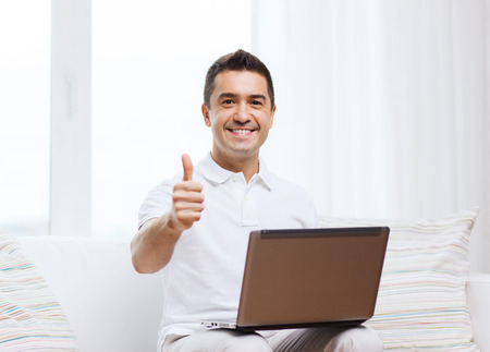people   lifestyle: technology, people lifestyle and networking concept - happy man with laptop computer showing thumbs up at home Stock Photo