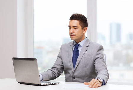 business, people and technology concept - smiling businessman in suit working with laptop computer in office