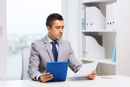 audit: business, people, paperwork and technology concept - businessman with tablet pc and papers in office