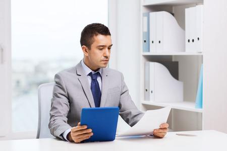 auditoria: negocio, la gente, el papeleo y el concepto de la tecnolog�a - hombre de negocios con Tablet PC y los papeles en la oficina