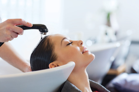 estilista: la belleza y el concepto de la gente - mujer joven feliz con la cabeza de lavado peluquero en el salón de pelo