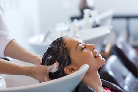 hairdressers: beauty and people concept - happy young woman with hairdresser washing head at hair salon Stock Photo