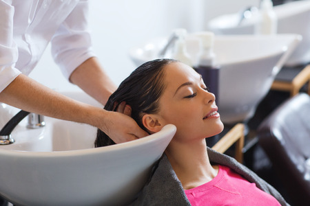 hair treatment: beauty and people concept - happy young woman with hairdresser washing head at hair salon Stock Photo