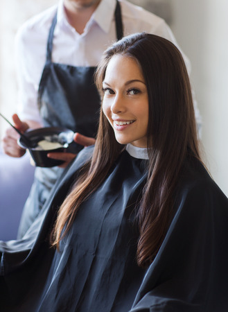 hair coloring: beauty and people concept - happy young woman with hairdresser coloring hair at salon
