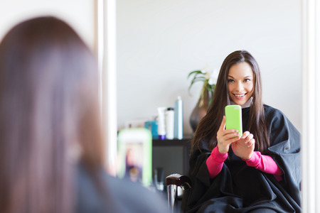 gadget: beauty and people concept - happy young woman with smartphone taking mirror selfie at hair salon Stock Photo