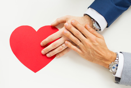 people, homosexuality, same-sex marriage, valentines day and love concept - close up of happy married male gay couple hands with red paper heart shape on table Stok Fotoğraf