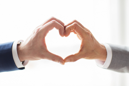 same sex: people, homosexuality, same-sex marriage, gesture and love concept - close up of happy male gay couple hands showing heart hand sign