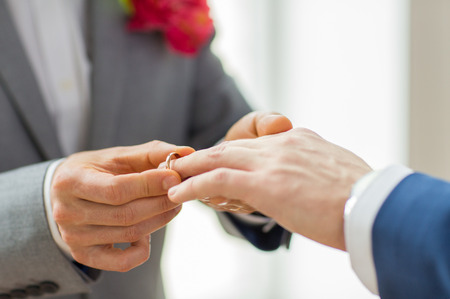 people, homosexuality, same-sex marriage and love concept - close up of happy male gay couple hands putting wedding ring on Stock Photo