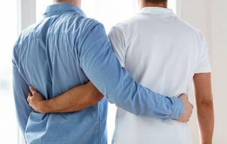sex: mensen, homoseksualiteit, het homohuwelijk, homo en liefde concept - close-up van gelukkige mannen homoseksueel stel knuffelen van achter