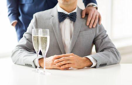 sex: Menschen, Feier, Homosexualität, die gleichgeschlechtliche Ehe und Liebe Konzept - in der Nähe in Anzügen von glücklich verheirateten Paar Homosexuell und Bogenbinder mit Sekt Gläser Hand auf die Schulter auf Hochzeit setzen