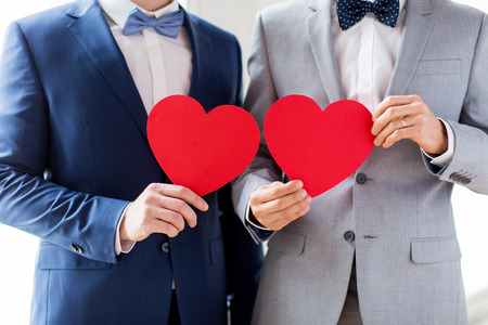 homosexual sex: people, homosexuality, same-sex marriage, valentines day and love concept - close up of happy married male gay couple holding red paper heart shapes on wedding