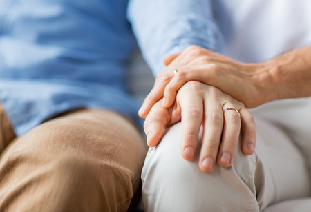 homosexual sex: people, homosexuality, same-sex marriage, gay and love concept - close up of happy male gay couple holding hands with wedding rings on Stock Photo