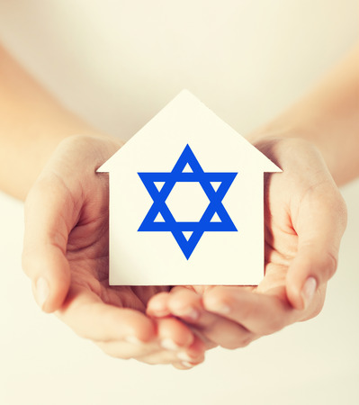 jewish community: religion, judaism and charity concept - female hands holding paper house with star of david symbol