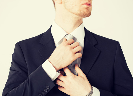 formal party: close up of man adjusting his tie.
