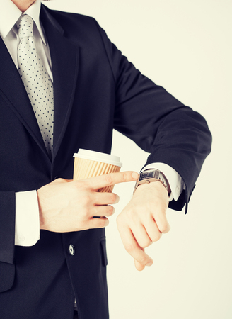 close up of man with take away coffee looking at wristwatch photo