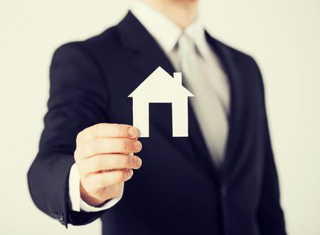 agente comercial: imagen del hombre de la mano que sostiene la casa de papel Foto de archivo
