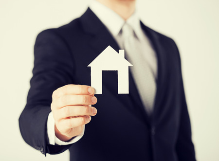 brokers: picture of man hand holding paper house