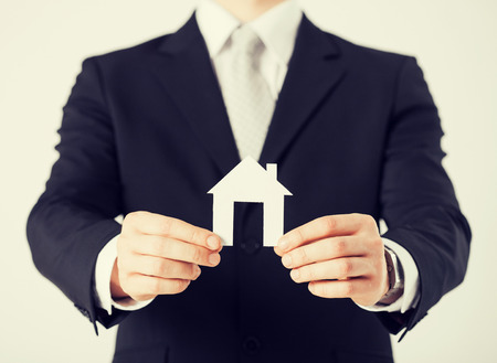 accommodation broker: picture of man hands holding paper house