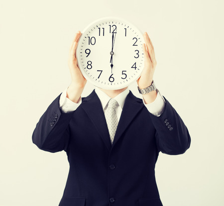 timezone: man covering his face with wall clock Stock Photo