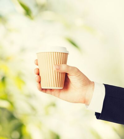 take time out: man hand holding take away coffee cup