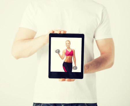 sport concept - man holding tablet pc with picture of woman doing exercise photo