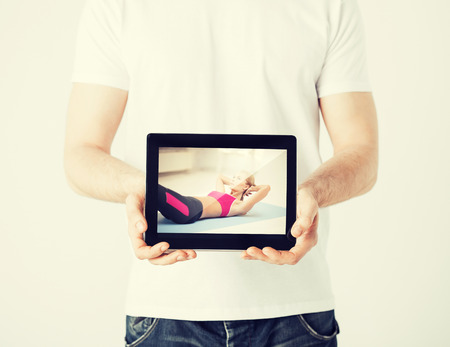 sport concept - man holding tablet pc with picture of woman doing exercise