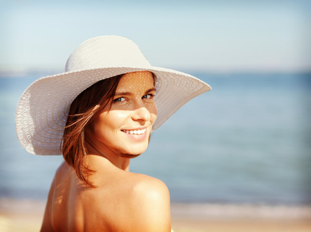 sun tan: summer holidays and vacation concept - girl in bikini standing on the beach
