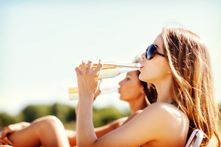 beer bottle: summer holidays and vacation - girls in bikinis with drinks on the beach chairs